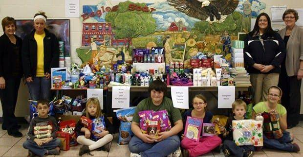 Making a Difference – The North Central Elementary students wanted to reach out and make a difference. In the spirit of the season and giving, students collected items for the Bryan Care and Rehabilitation Center, Evergreen Manor Nursing Home and the Williams County Humane Society. Shown with the collected items are front row: Talen Denstedt, Lauren Pfund, Luke Pickford, Aleegan Kelly, Dreyden Endicott, and Sydni Peel. Back row: Lisa Blue (NC teacher), Krystal Gibbs from the Williams County Humane Society, Marci Tomblin from Evergreen Manor Nursing Home and Mary Smith (NC teacher).