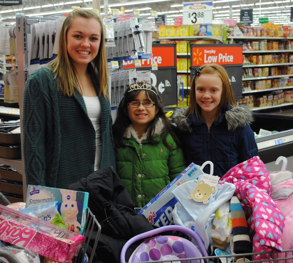 GIVING BACK ... The Miss West Unity Queens spent the holidays giving back to a local family in need. From clothing to toys to food, the girls shopped, wrapped and delivered a wonderful holiday surprise. Shown with a cart full of goodies are Miss West Unity Emily Maneval, Little Miss West Unity Brianna Bell and Junior Miss West Unity Jayla Stannard.